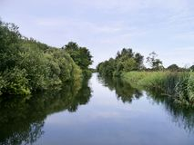 Looking down river with tree lined banks. Another area of the Norfolk Broads, England Royalty Free Stock Images