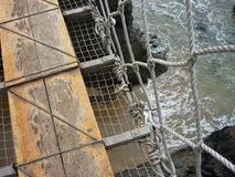 Looking down from a rope bridge. The famous rope bridge in Carrick-a-Rede in Northern Ireland, one of the most popular tourists attraction stock image