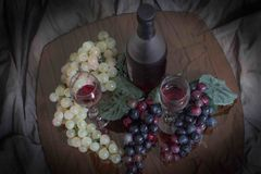 Looking down of a table of wine and grapes. A table set for two, garnished with grapes and your favorite wine waiting to be poured into a sparkling wine glass Royalty Free Stock Photo