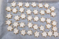 Looking down on tray of ready to bake cinnamon star Christmas co. Okies with glazing on baking paper - uncooked, messy and untidy stock image