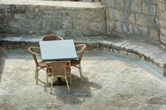 Looking down on wicker table and chairs in a ctone courtyard sum Stock Photo
