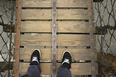 Looking Down from a wooden suspension bridge stock images