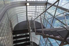 Looking downwards in an open stairwell of a modern building. Looking downwards in an open stairwell of a modern office building Royalty Free Stock Images