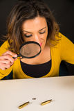 Looking for evidence. Woman with magnifying glass looking for evidence among fingerprints and bullet shells, a conceptual shot stock photos