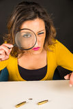 Looking for evidence. Woman with magnifying glass looking for evidence among fingerprints and bullet shells, a conceptual shot royalty free stock photo