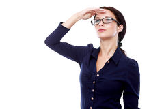 Looking far away. Young business woman in glasses looking far away cover her eyes from the sun, over a white background Royalty Free Stock Image