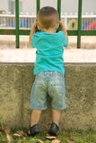 Looking through the fence. Boy looking through a fence, seen from behind royalty free stock images
