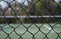 Looking through fence at tennis court stock image