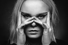 Looking through fingers. Serious woman looking at camera through fingers mask, monochrome Stock Photography