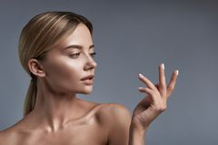 Calm lady looking at her fingers and thinking royalty free stock images