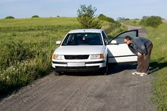 Looking at flat tire. A man looking at his car's tyre, checking if it is fine. Country road, white car stock photo