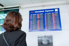 Looking at flight information board Stock Photos