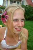 Looking flower. Beautiful young blonde girl with flower in hair Stock Photo
