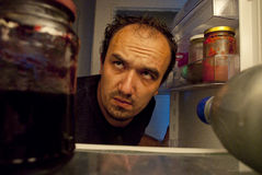 Looking for food. Tired man looking for a midnight snack into the fridge Stock Image