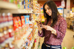 Looking at the food label. Cute young woman examining a product label while shopping at the store stock photos
