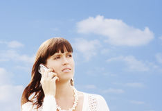 Looking forward. Young girl with mobile phone against sky Stock Image