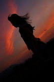 Looking forward. Silhouette of girl is looking forward with sunset behind stock image