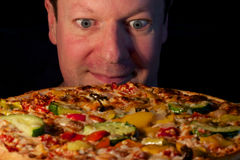 Looking forward to have a vegetarian pizza. Middle-aged man happily looking forward to have his vegetarian pizza on a plate in front of him Royalty Free Stock Image