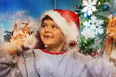Boy behind decorate window before Christmas Stock Image