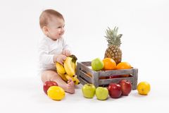 Looking at fruit cute smiling baby on white background among fru Royalty Free Stock Photography