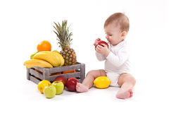 Looking at fruit cute smiling baby on white background among fru. Its. Photo with depth of field Royalty Free Stock Photos