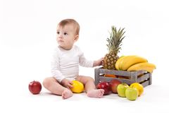 Looking at fruit cute smiling baby on white background among fru Royalty Free Stock Image