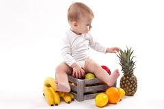 Looking at fruit cute smiling baby on white background among fru Royalty Free Stock Images