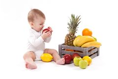 Looking at fruit cute smiling baby on white background among fru Stock Photography