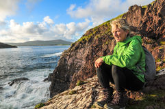 Looking for Fungi. Mature woman sitting on cliff above Dingle Bay looking for Fungie, Dingles world famous Dolphin Stock Photos