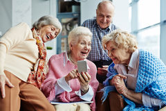 Looking through funny photos. Four cheerful elderly people hanging out in spacious coffeehouse and looking through photos on modern smartphone Stock Image