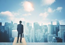 Looking at future city. Businessman standing on a roof and looking at future city Royalty Free Stock Images