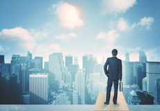 Looking at future city. Businessman standing on a roof and looking at future city Royalty Free Stock Photo