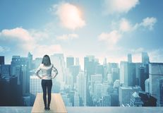 Looking at future city. Businesswoman standing on a roof and looking at future city Stock Photo