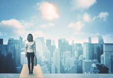 Looking at future city. Businesswoman standing on a roof and looking at future city Stock Image