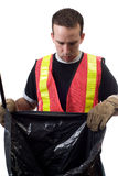 Looking For Garbage. A young worker wearing a reflective vest is looking inside a garbage bag, isolated against a white background Stock Image