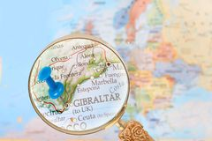 Looking in on Gibraltar, United Kingdom. Blue tack on map of Europe with magnifying glass looking in on Gibraltar, United Kingdom Royalty Free Stock Photo