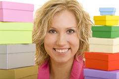 Looking through gifts. Young woman holding two stacks of gift boxes royalty free stock images