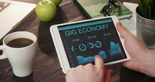 Looking at gig economy information using tablet computer. At the desk stock video footage