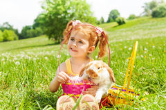 Looking girl with cute rabbit and baskets in park Stock Photos