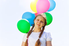 Looking girl with flying balloons in the air Stock Photos