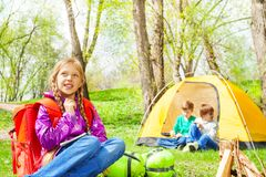 Looking girl with red backpack rests in camp Stock Images