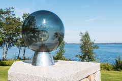 Looking through a glass orb overlooking Penobscot Bay Maine. A glass orb with a lightbulb inside and a view of Penobscot Bay with the sun and trees reflecting Stock Images