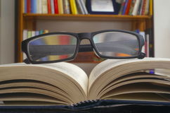 Looking glasses on an open book. Ans a bookshelf on background stock photos