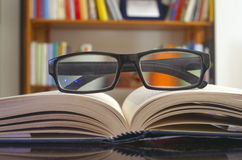Looking glasses on an open book. Ans a bookshelf on background stock photo