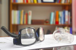 Looking glasses on an open book. Ans a bookshelf on background royalty free stock photos