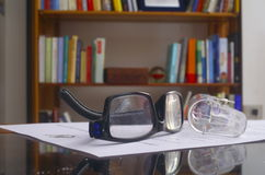 Looking glasses on an paper sheet and books in the background. Black Looking glasses on a paper sheett and a bookshelf in the background stock photography