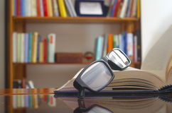 Looking glasses on an open book. Ans a bookshelf on background stock photography