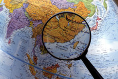 Looking at globe using magnifying glass (Asia Region) Royalty Free Stock Photography