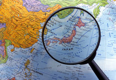Looking at globe using magnifying glass (Asia Region) Royalty Free Stock Photo