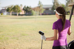 Looking at the golf course. Young female golfer looking at the golf course with copy space Stock Image